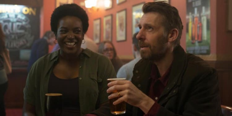 Still from the film Killed by my Debt, featuring characters drinking at a pub