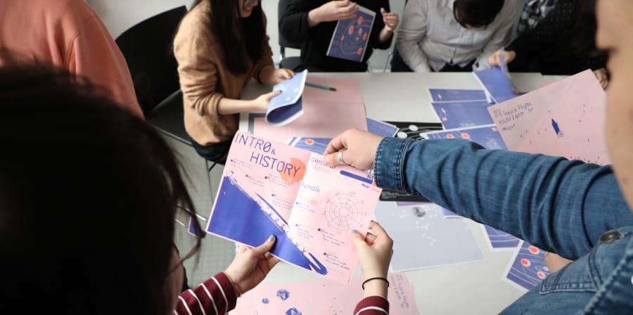 Students folding prints to make their data visualisation zine