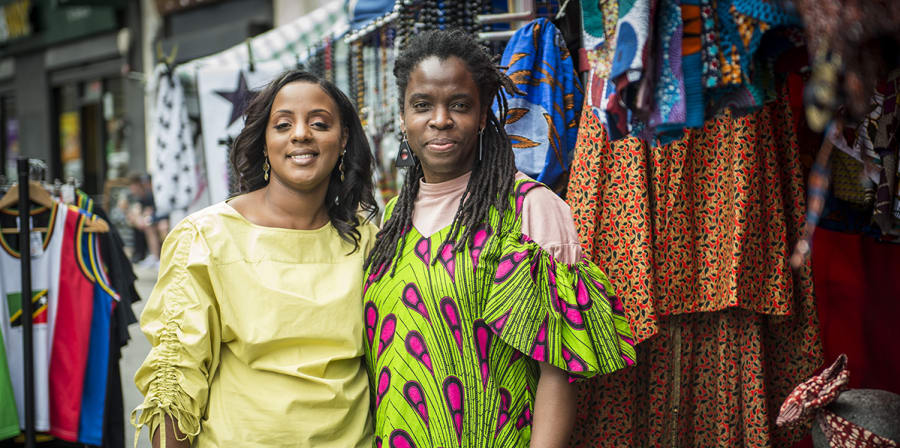 Image depicts two women standing in front of clothes styles as part of the It's Your Local Market project.