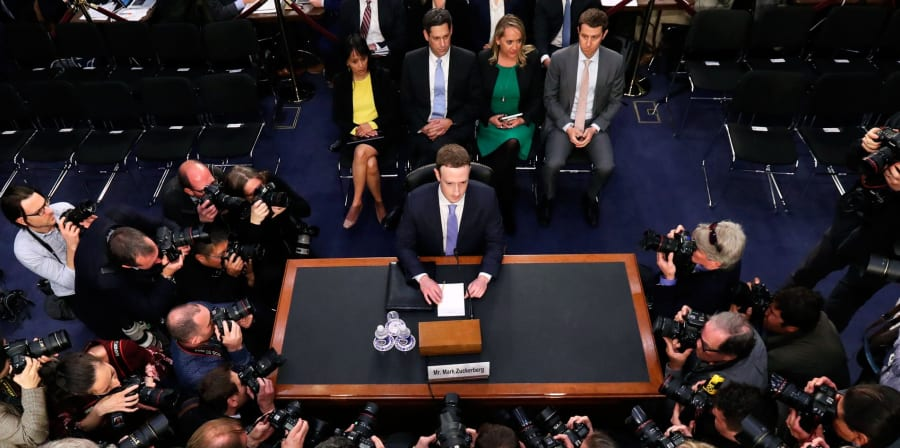Mark Zuckerberg, CEO of Facebook, sits at a table testifying before Congress.