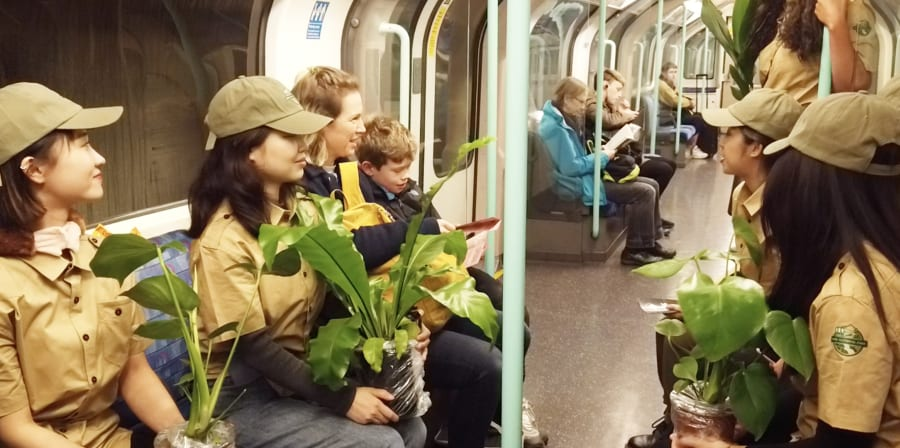Students dressed as park rangers on a tube train carrying plants and talking to passengers