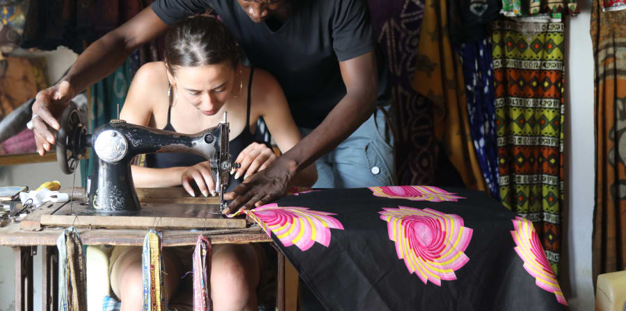 Student being taught how to use sewing machine as part of Route-Artlantique project