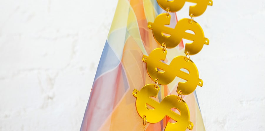 Multicoloured material with metal dollar signs hanging vertically down.
