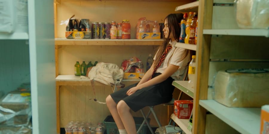 A student waits in a shop's stock-room.