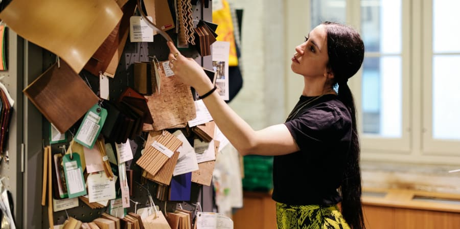 A student looking at fabric samples and materials in the library