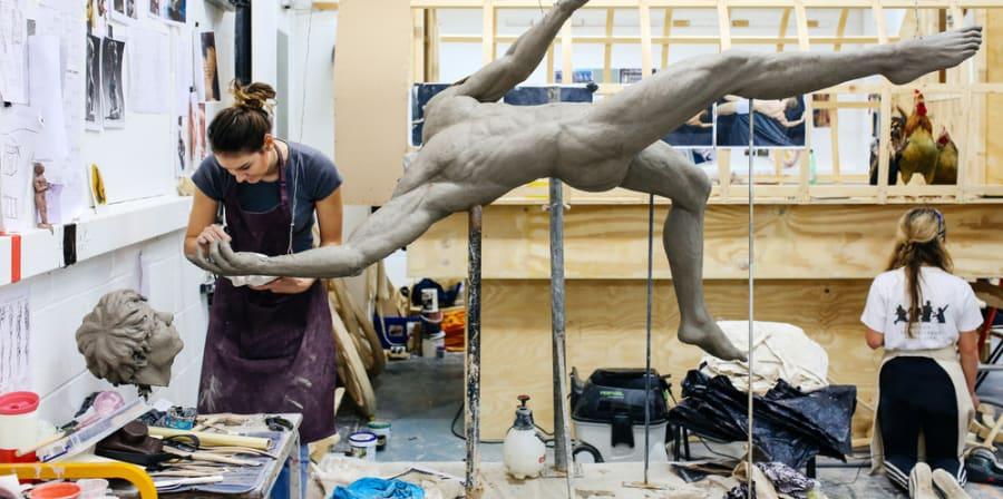 Artist working on her sculpture in a cluttered fine art studio.