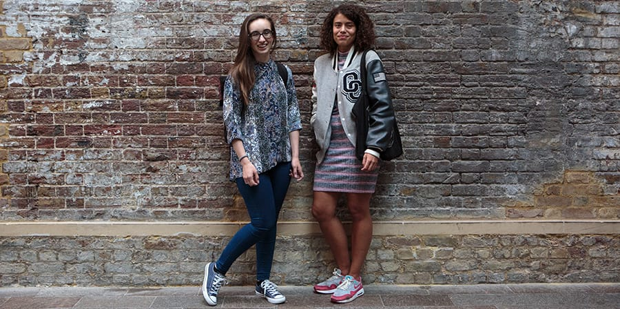 Photo of two females students standing in front of a brick wall