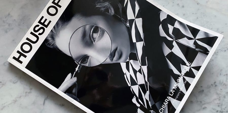 A magazine cover featuring a woman in a black and white-check clothes.