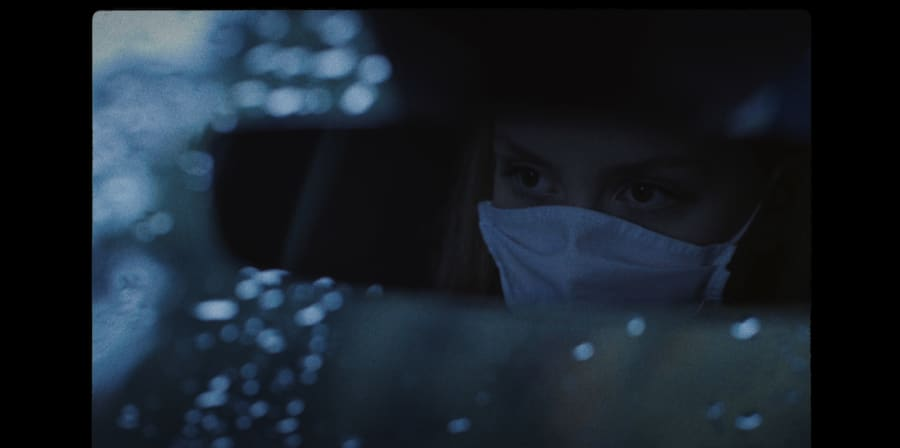 A girl wears a face-mask in a car.