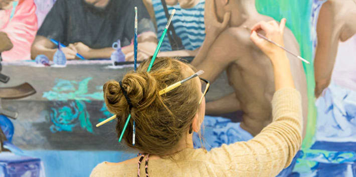 A person with paintbrushes in their hair, painting onto a large canvas