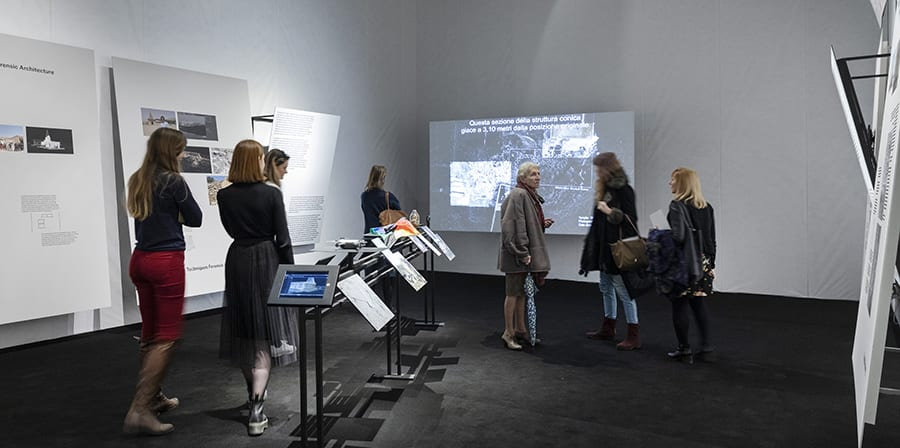 Photo of Maps of Defiance exhibition with visitors and panels.