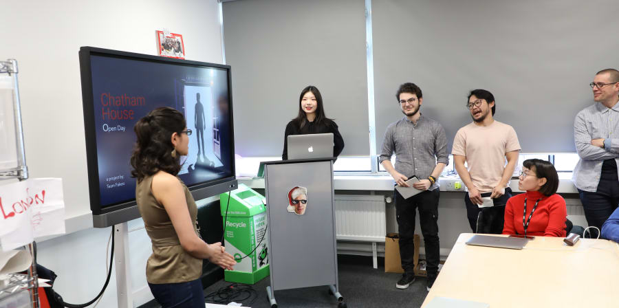 Photo of UX Design students presenting design proposals.