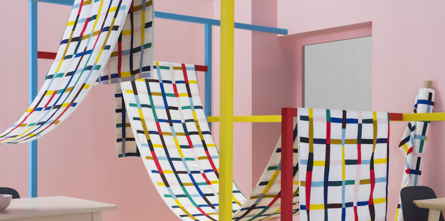 pink set of walls with colourful grid structure with fabric draped across
