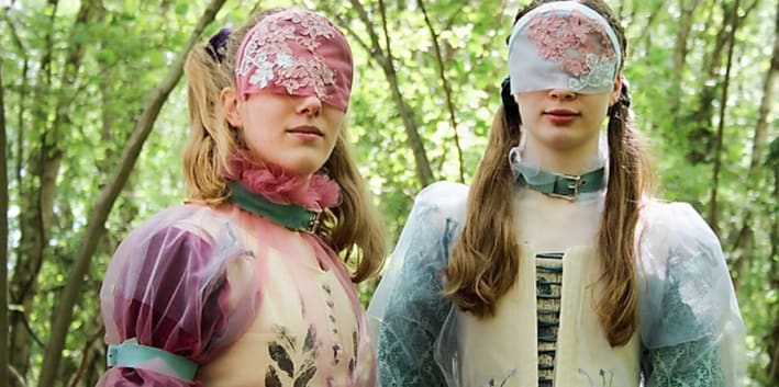 two masked models face the camera while in a forest looking away from the camera wearing garments inspired by the pre-Raphaelite art movement