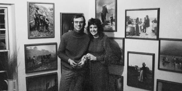 Two people standing in front of a wall of photographs