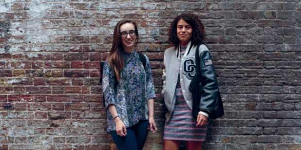 Two students standing in front of a brick wall