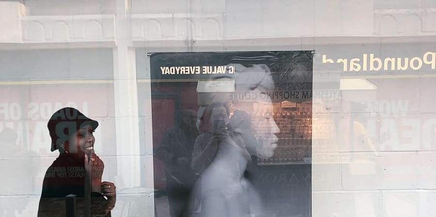 Rayvenn Shaleigha D'Clark in gallery with print hanging through the window