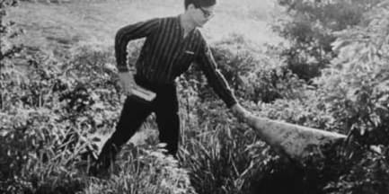 man cutting grass in a black and white