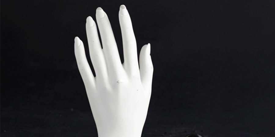 Mannequin hand peaking out of black sand
