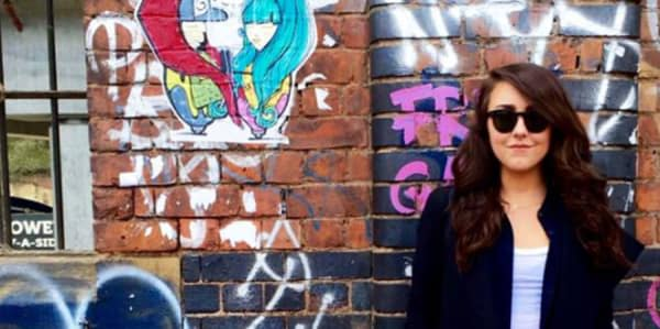 Elizabeth Delaney standing in front of a wall with graffiti on