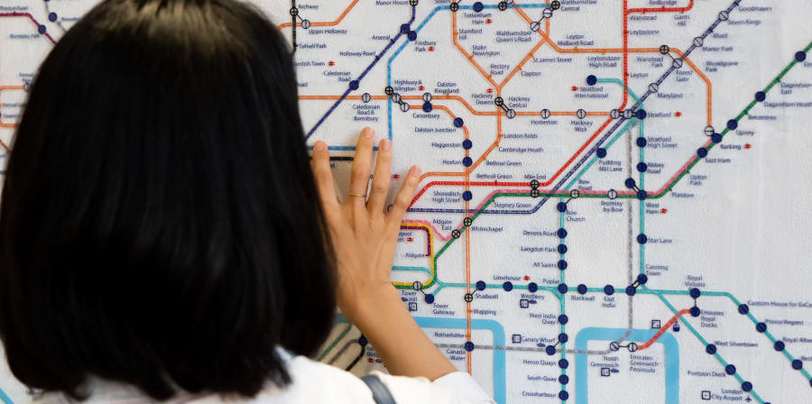 Female student seen from behind with hand reaching up to read braille London Tube map
