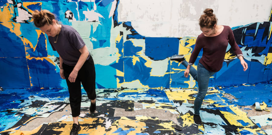 Two artists create work in a room covered in blue, yellow and white squares.
