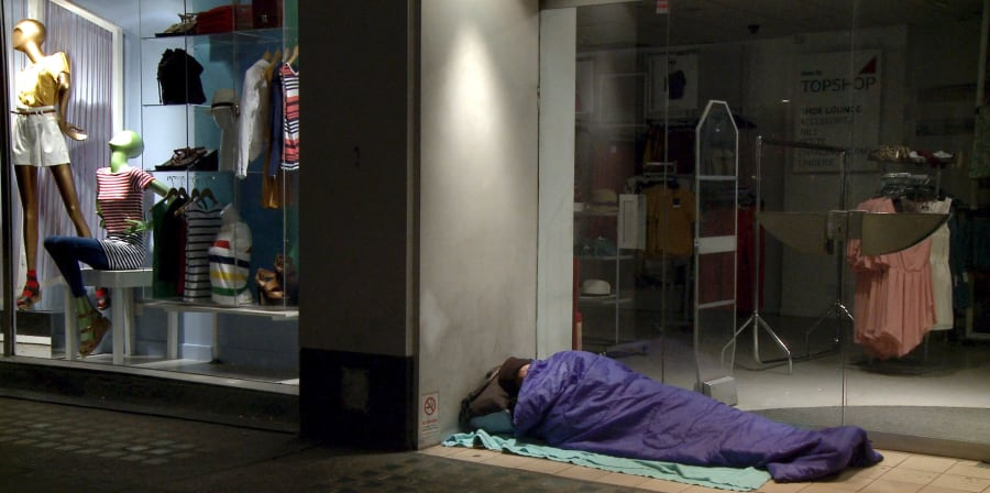 Movie still of a homeless person sleeping in a shop corner