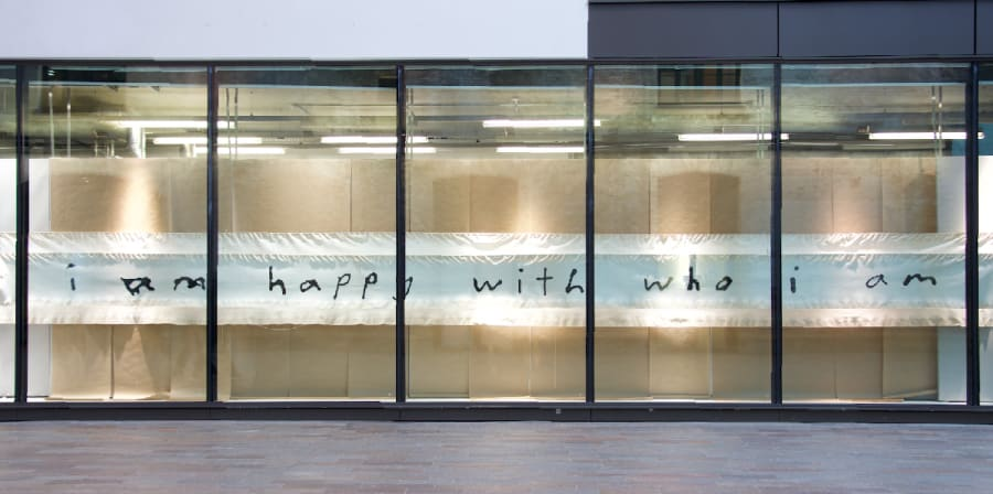 windows show long banner embroidered words read i am happy with who i am