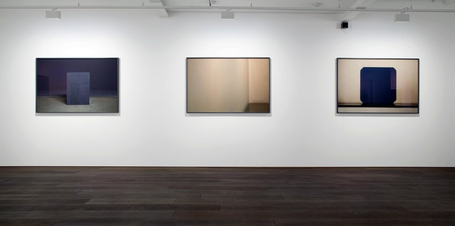 Three paintings sit on a gallery wall.