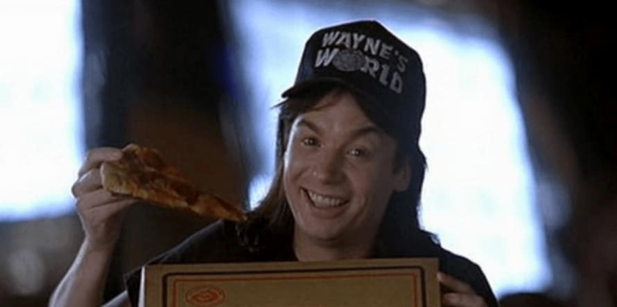 Still from the film Wayne's World, showing Wayne posing with a pizza from Pizza Hut.