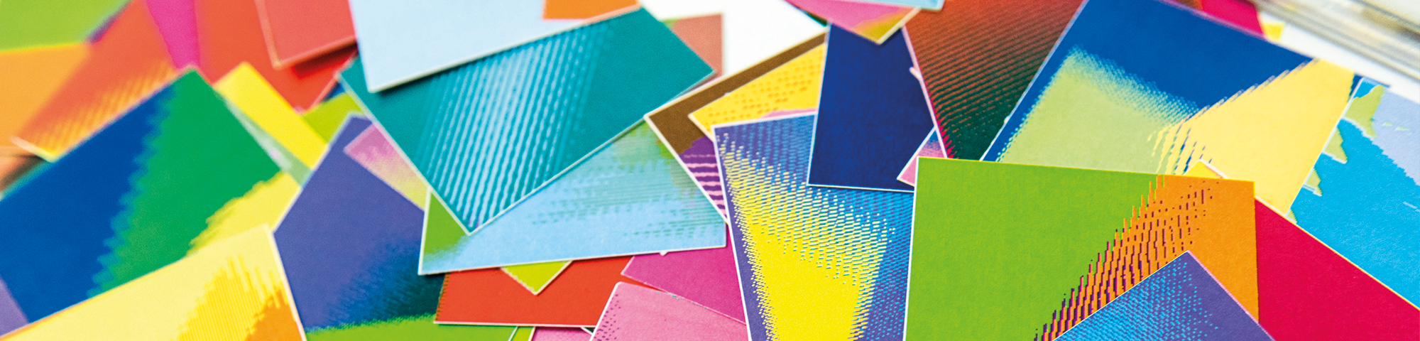 Image of various multicoloured sheets of card scattered across a table.