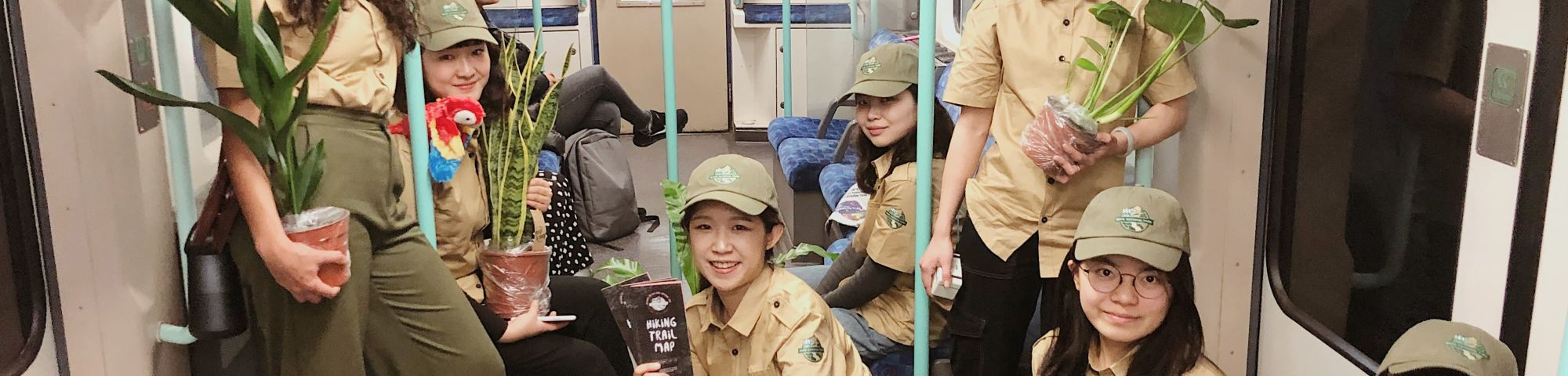 A group of students dressed as park rangers hold otted plants on a tude train