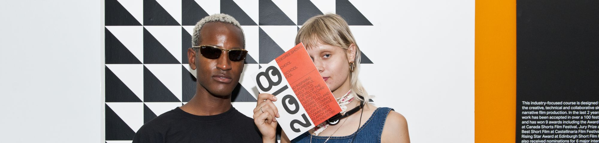 Two students stand in front of a monochrome patterned wall at a Degree Show event at LCC.