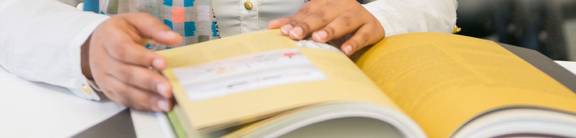 Close up shot of a book on a table and a pair of hands holding it open