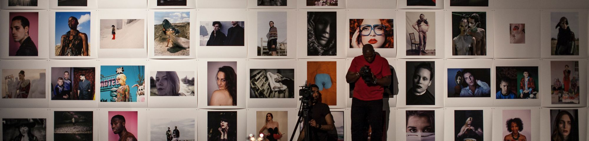 Collage of photos against a white wall with a man standing infron