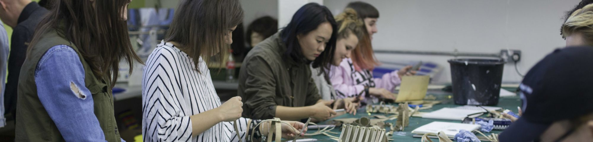 Students at a workbench using materials to create models