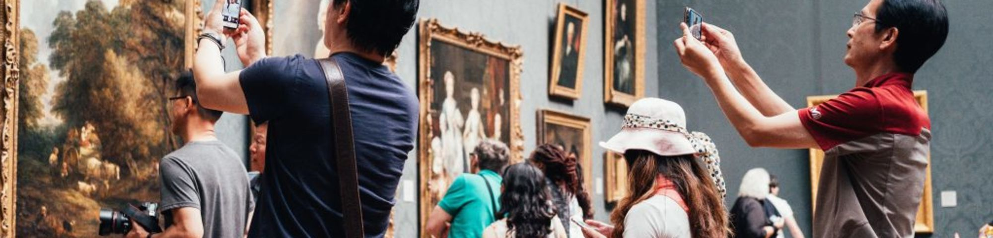 people photographing a painting in a museum
