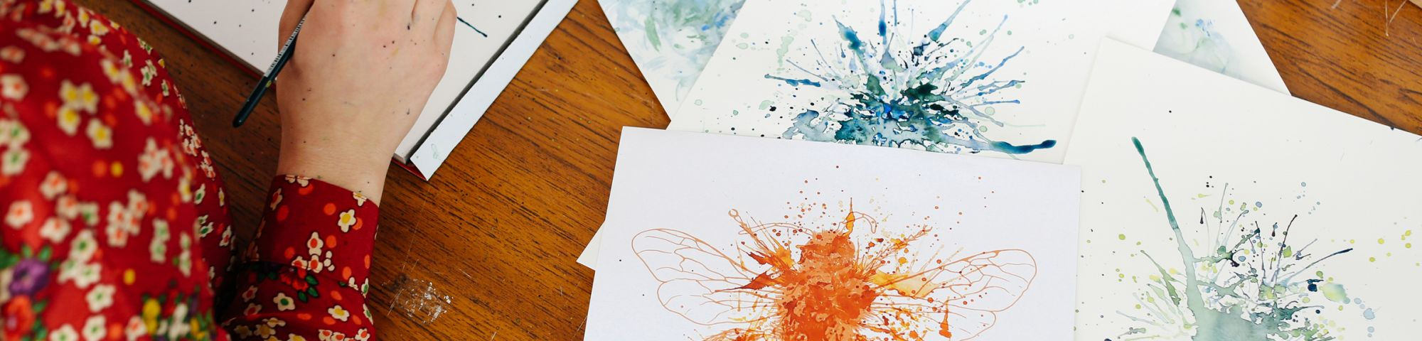 Hand with a paintbrush in and pieces of paper with blue and orange paintings on