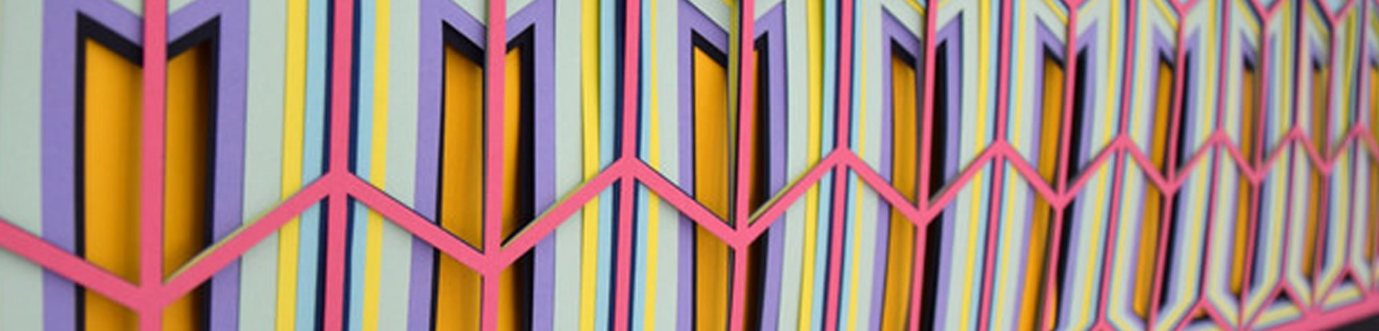 Close up side view of a colourful piece of art in orange, white and pink hanging on a wall