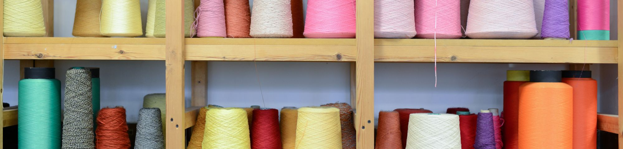 Spools of pink, yellow, blue and orange thread on a shelf