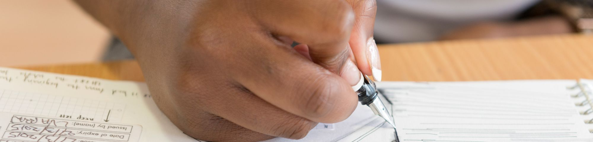 Close up shot of a hand holding a pen that is drawing on paper