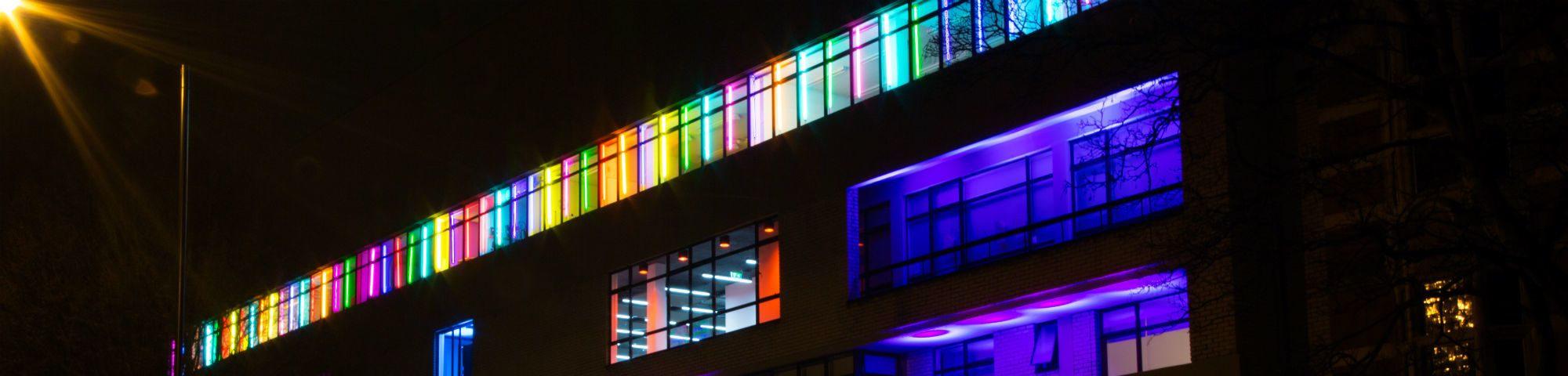 A landscape picture of a building at our Camberwell Campus with multi coloured lights at night.
