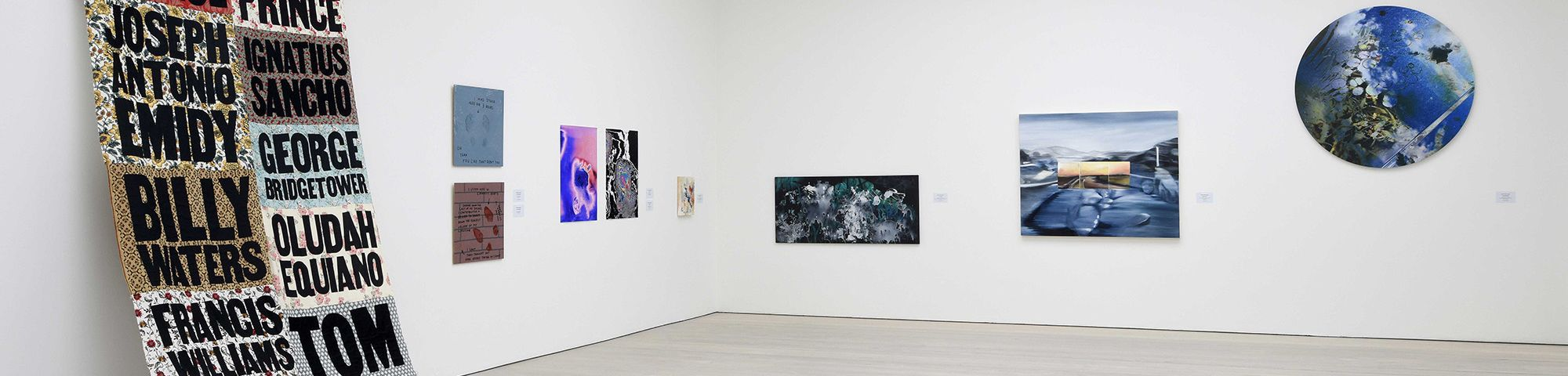 Installation view of several paintings and one large quilt hung on white wall