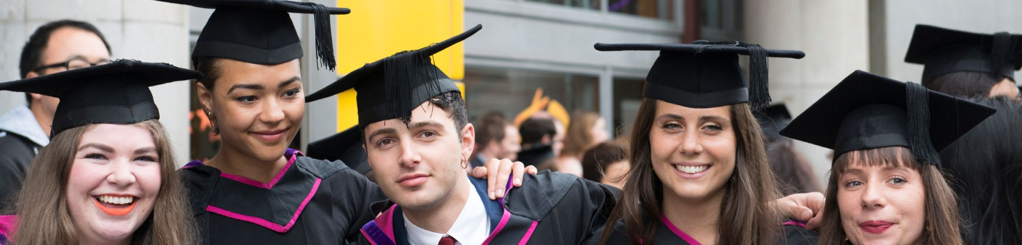 A group of students wearing graduation robes and mortarboard caps after graduating from University of the Arts London UAL