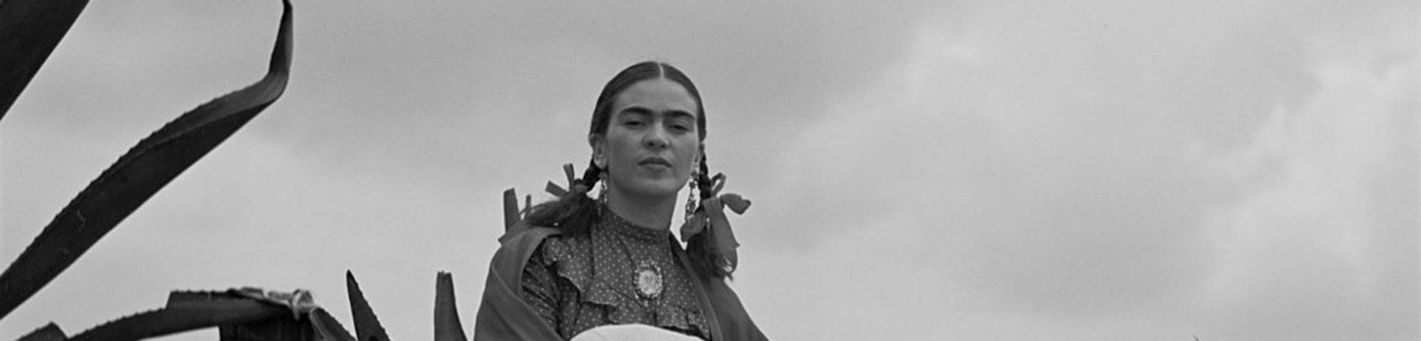 Frida Kahlo seated next to an agave plant, during a photo shoot for Vogue magazine