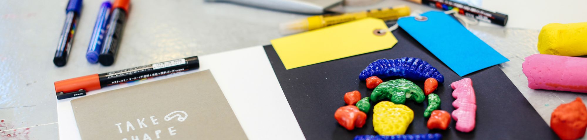 Moulded pieces of colourful clay on a piece of paper with pens and labels next to it