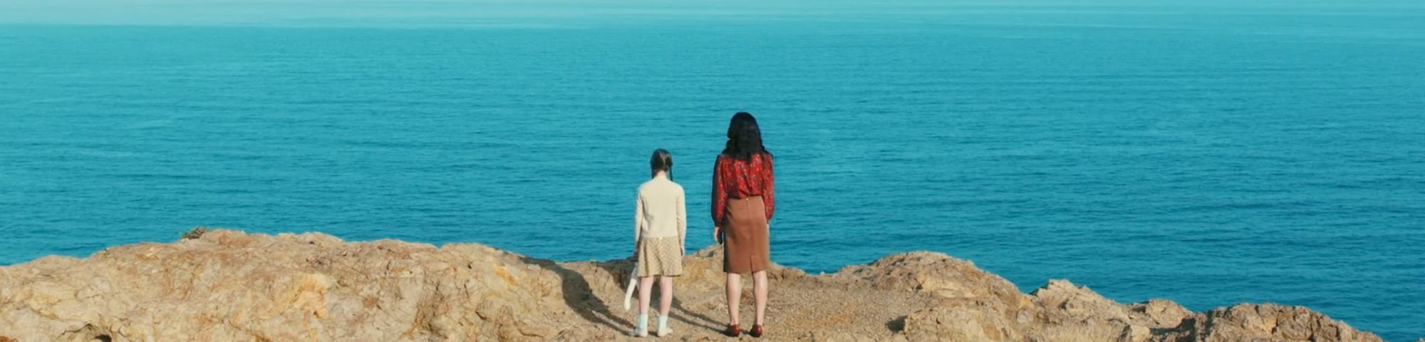 Screen shot from a film of two people standing on a cliff looking out into the sea.