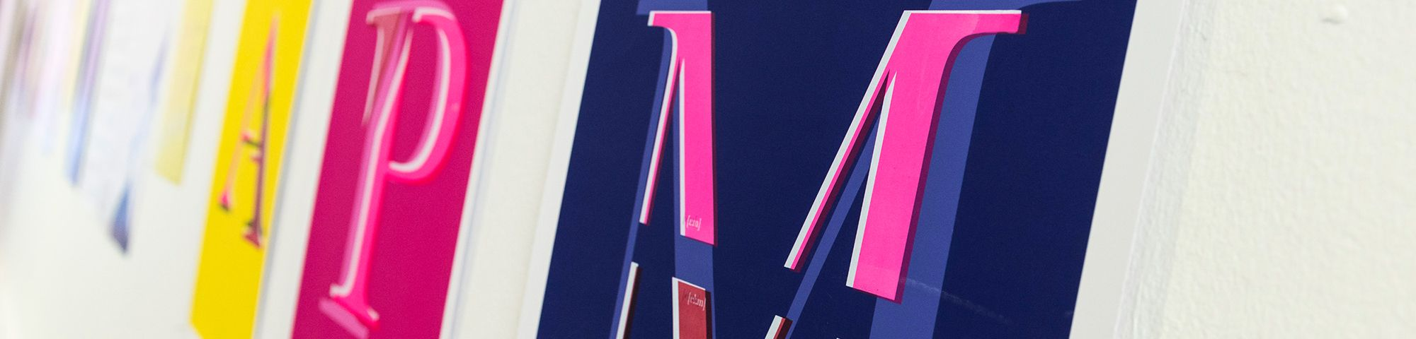 Installation image of graphic screen-printed posters in a range of colours