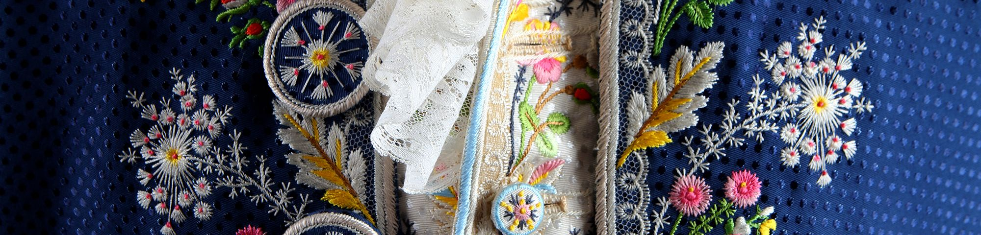 Detail image floral embroidery in pink, yellow, whilte and green on a blue silk background.