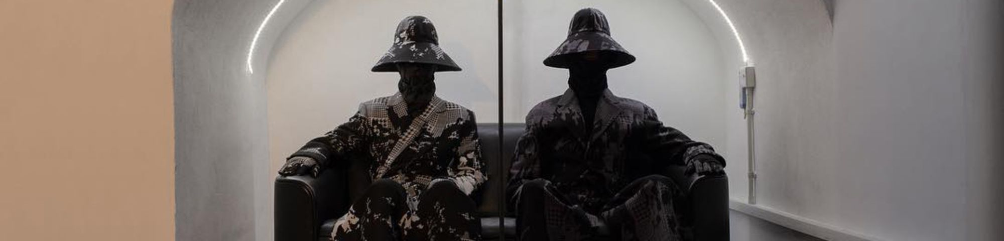 Two models wearing the same clothes with big hats and their faces covered, sitting side by side on two arm chairs
